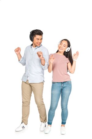 happy asian couple looking at each other while listening music in headphones and dancing on white background Imagens