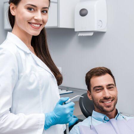 beautiful and happy dentist holding dental equipment near happy man 写真素材