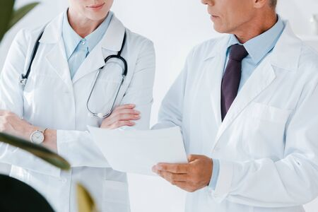 cropped view of doctor holding blank paper near colleague with crossed arms