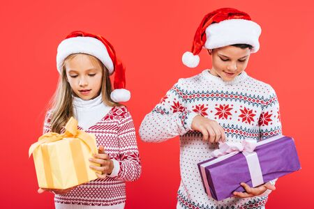 front view of two smiling kids in santa hats with presents isolated on red
