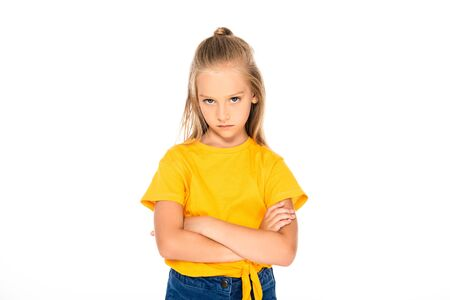 displeased child looking at camera while standing with crossed arms isolated on white