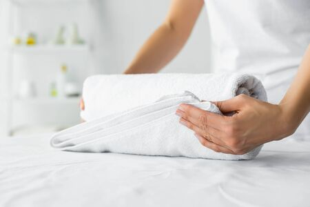 cropped view of masseur holding white towel in spa