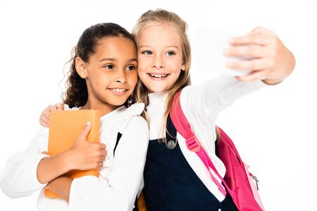 happy schoolgirl taking selfie while hugging african american friend isolated on white 写真素材 - 131880740