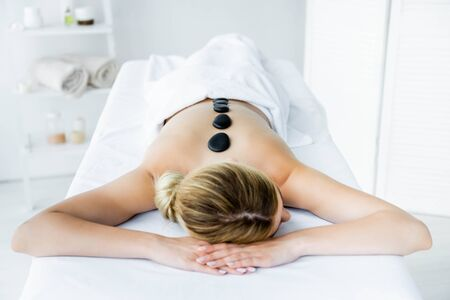 woman with hot stones on back lying on massage mat Stok Fotoğraf