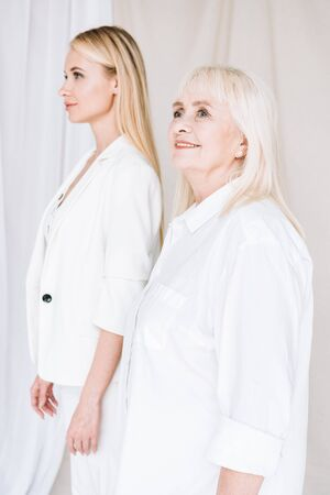 selective focus of blonde grandmother and granddaughter together in total white outfits