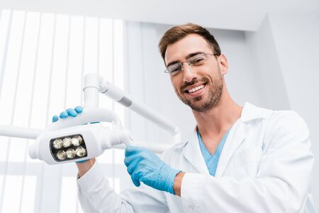 low angle view of cheerful dentist in glasses touching medical lamp and looking at camera