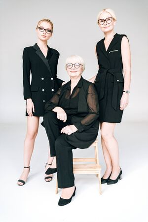 full length view of fashionable three-generation blonde businesswomen in glasses with crossed arms isolated on grey 스톡 콘텐츠