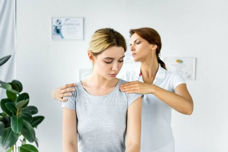 chiropractor touching shoulders of attractive patient in grey t-shirt