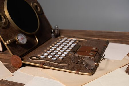 steampunk laptop, glasses and documents on wooden table isolated on grey 版權商用圖片