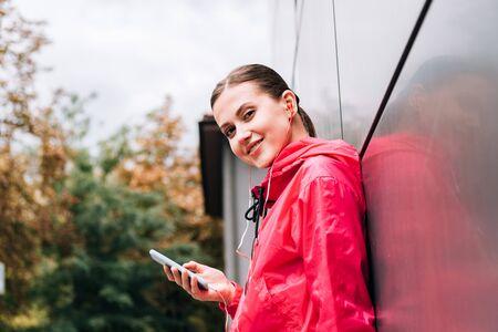 smiling sportswoman listening music in earphones and using smartphone on street