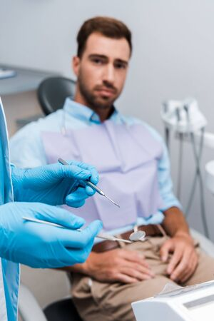 selective focus of dentist in blue latex gloves holding dental instruments near man