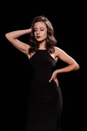 Jeune femme en robe debout avec la main sur la hanche isolated on black
