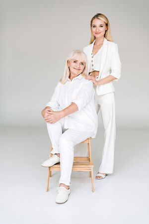 full length view of happy blonde grandmother sitting on chair near granddaughter in total white clothes