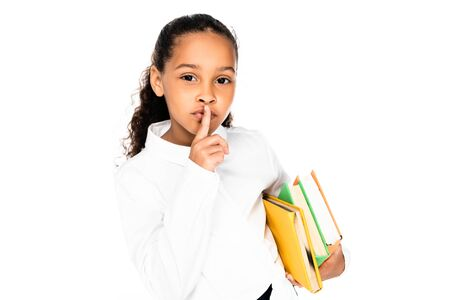 adorable african american schoolgirl holding books and showing hush gesture isolated on white