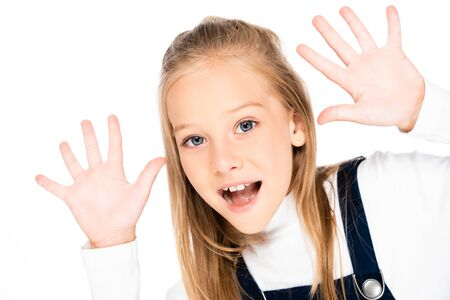 cheerful schoolgirl showing chalk stained hands while looking at camera isolated on white