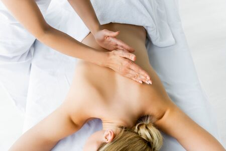 cropped view of masseur doing back massage to woman in spa Фото со стока - 131832915