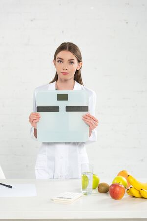 front view of dietitian in white coat holding digital scales 写真素材