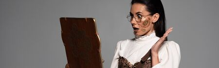 panoramic shot of shocked steampunk woman in glasses looking at vintage laptop screen isolated on grey