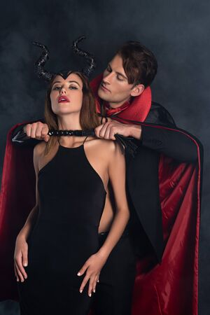 handsome man in vampire halloween costume holding flogging whip near girl with horns on black with smoke