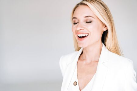 happy beautiful young blonde woman in total white outfit with closed eyes isolated on grey