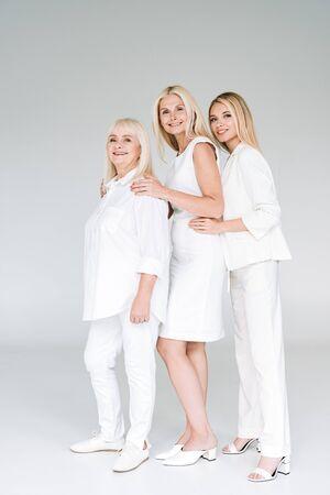 full length view of three generation blonde women posing on grey