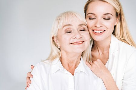 happy blonde grandmother and granddaughter together in total white outfits with closed eyes embracing isolated on grey