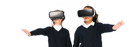 panoramic shot of two multicultural schoolgirls using virtual reality headsets isolated on white 写真素材 - 131881248