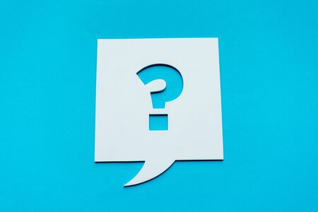 top view of question mark on white speech bubble isolated on blue