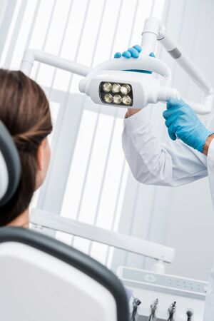 cropped view of dentist in latex gloves touching medical lamp near patient