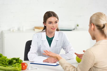 smiling dietitian in white coat looking at patient at table