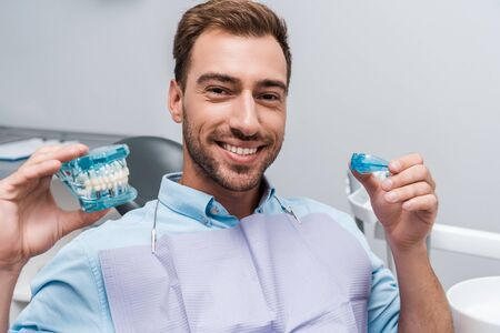 happy bearded man holding retainer and teeth model in hands