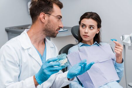 selective focus of handsome dentist in glasses gesturing near woman with retainer