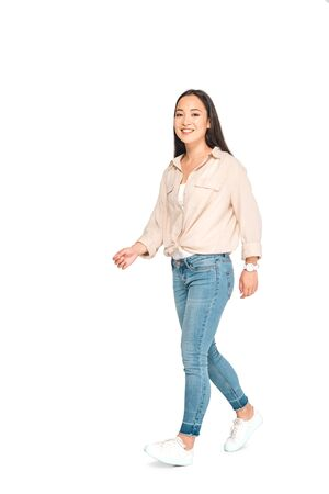 attractive asian woman in blue jeans looking at camera while walking on white background