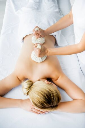 cropped view of masseur doing back massage with herbal balls to woman in spa