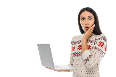 surprised woman looking at camera while holding laptop isolated on white
