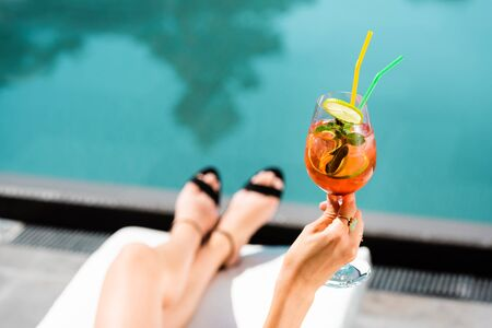Cropped view of woman near swimming pool with cocktail on resort