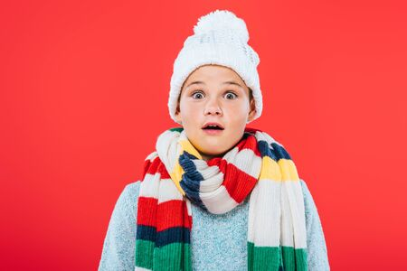 front view of shocked kid in hat and scarf isolated on red