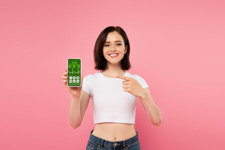 smiling girl pointing with finger at smartphone with healthcare app isolated on pink