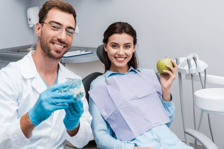 selective focus of cheerful dentist in glasses holding teeth model near happy woman with green apple