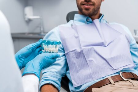 cropped view of dentist in latex gloves holding teeth model near patient