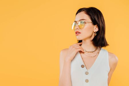 elegant woman in sunglasses posing isolated on yellow
