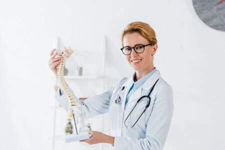 cheerful doctor in glasses holding spine model and smiling in hospital