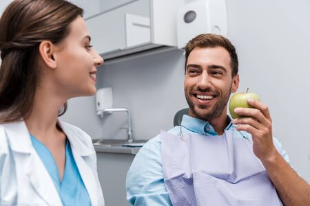 selective focus of happy man holding apple near cheerful woman