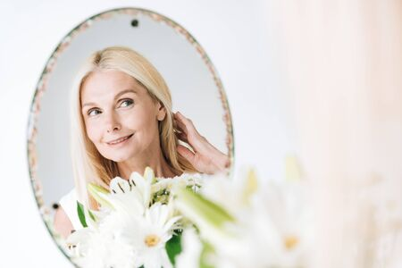 happy blonde mature woman with flowers looking through mirror isolated on white