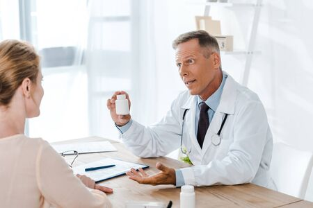 doctor in white coat sitting and gesturing while holding bottle and looking at woman