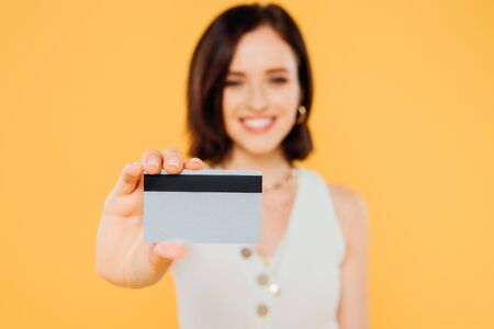 selective focus of smiling elegant girl holding credit card isolated on yellow