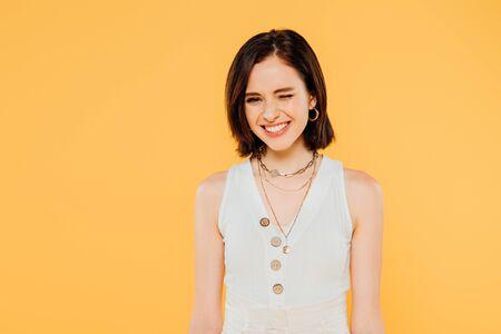 smiling elegant girl winking isolated on yellow