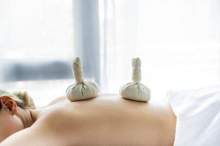 woman lying on massage mat with herbal balls on back