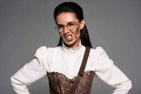 angry steampunk woman in glasses with makeup looking at camera isolated on grey