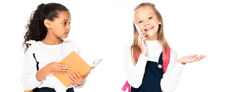 panoramic shot of displeased african american schoolgirl looking at cheerful friend talking on smartphone isolated on white